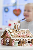 Decorated gingerbread house, small girl in background