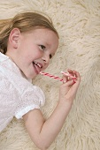 Small girl eating candy cane