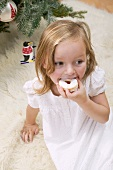 Small girl eating jam biscuit