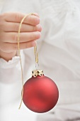 Child holding Christmas bauble with gold string