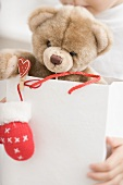 Child holding teddy bear in paper carrier bag