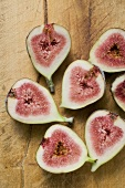Several fig halves on wooden background