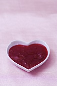 Strawberry jam in heart-shaped dish