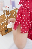 Small girl decorating gingerbread house using piping bag