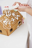 Child decorating gingerbread house using piping bag