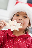 Small girl in Father Christmas hat holding Christmas biscuit