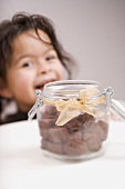 Chocolate biscuits in storage jar, child in background