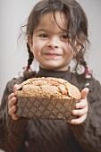 Small girl holding Christmas cake