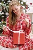 Frau öffnet Weihnachtspaket