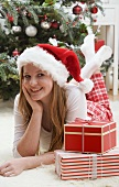 Woman in Father Christmas hat beside Christmas gifts