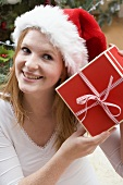 Woman in Father Christmas hat holding Christmas gift