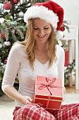 Woman in Father Christmas hat looking at Christmas gift