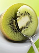 Spooning the flesh out of a kiwi fruit