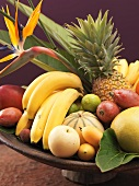Exotic fruit still life in wooden bowl (close-up)