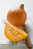 Hokkaido pumpkins (whole and quarter) on tea towel, knife