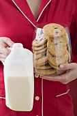 Woman holding glass full of cranberry cookies & bottle of milk