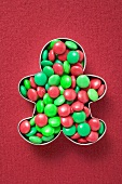 Red and green chocolate beans in biscuit cutter