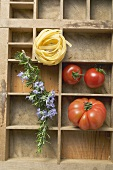 Ribbon pasta, tomatoes and rosemary in type case