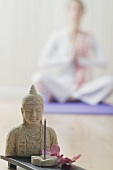 Buddha statue & incense sticks, woman sitting cross-legged