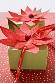Two Christmas parcels decorated with red paper flowers