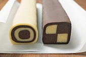 Two rolls of chocolate and plain dough on baking parchment