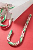 Candy canes in and beside paper bag