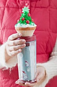 Woman holding cupcake on insulated beaker (Christmas)