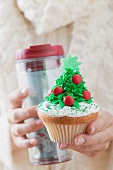 Woman holding cupcake and insulated beaker (Christmas)