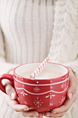 Woman holding cup of cocoa with candy cane (Christmas)