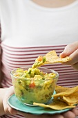 Woman dipping tortilla chip in guacamole