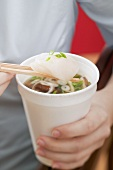 Woman holding paper cup of Asian noodle soup