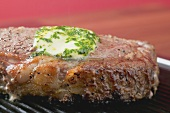 Beef steak with herb butter on barbecue (close-up)