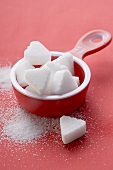 Heart-shaped sugar lumps in red measuring cup