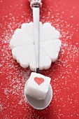 Heart-shaped sugar lumps in a circle, sugar cube on spoon