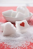 Sugar cube with red heart and heart-shaped sugar lump