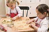 Two small girls cutting out biscuits