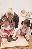 Woman and two small girls cutting out chocolate biscuits