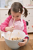 Small girl stirring mixture in mixing bowl