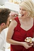 Mann füttert Frau mit Zimtstern