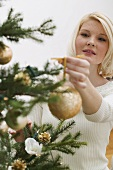 Woman hanging gold bauble on Christmas tree