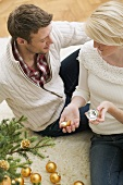 Couple beside Christmas tree, woman holding broken bauble