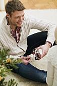 Paar neben Christbaum, Mann öffnet Weihnachtspäckchen