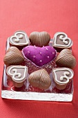 Purple fabric heart surrounded by chocolates