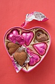 Pink chocolates in heart-shaped box (one partly eaten)