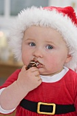Baby in Father Christmas hat eating chocolate