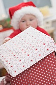 Baby in Father Christmas hat opening Christmas parcel