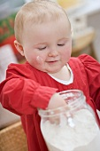 Toddler reaching into jar of flour