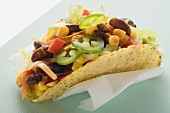 Taco filled with sweetcorn and beans on paper napkin