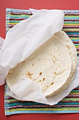 Freshly-baked tortillas on kitchen roll (Mexico)