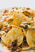Tortilla chips with melted cheese and olives
